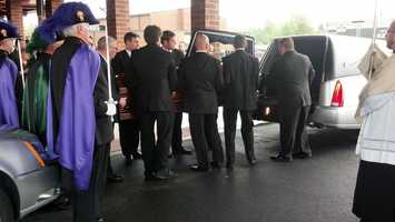 McFadden's coffin is placed in a hearse.