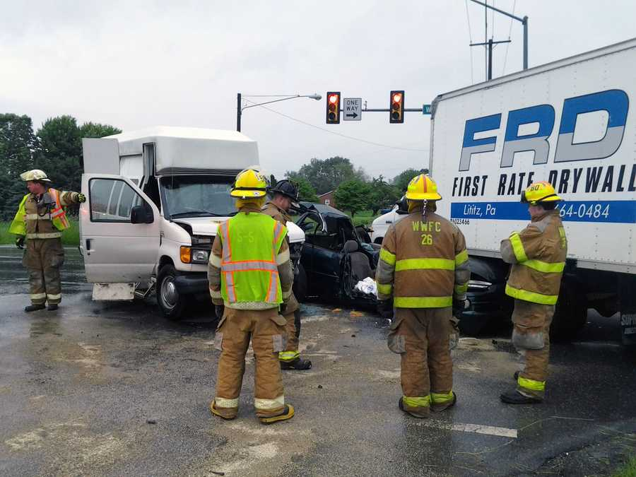 The van collided with the car, pushing it into the truck, police said.