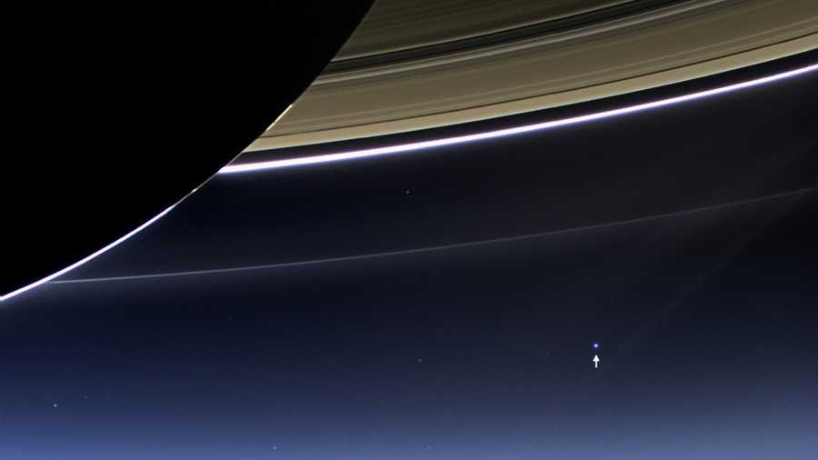 In this rare image taken on July 19, 2013, the wide-angle camera on NASA's Cassini spacecraft has captured Saturn's rings and our planet Earth and its moon in the same frame.Earth, which is 898 million miles (1.44 billion kilometers) away in this image, appears as a blue dot at center right&#x3B;&#x3B; the moon can be seen as a fainter protrusion off its right side. An arrow indicates their location.