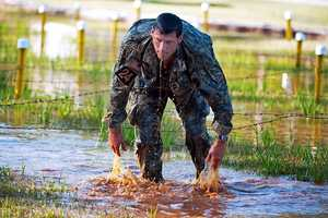 """20. Master Sgt. Christopher Nelms, United States Army Special Operations Command, Headquarters, Headquarters Company (HHC USASOC), finishes a low craw under the """"Worm Pit"""" at the Malvesti Obstacle Course in the Best Ranger Competition, April 13, 2013 at Fort Benning."""