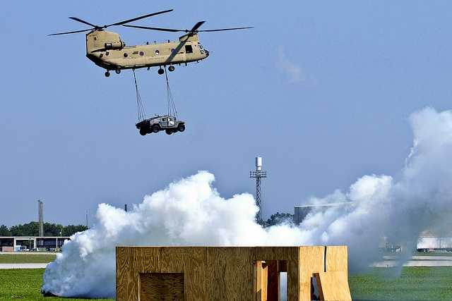 43. Two Humvees dangle below a CH-47 Chinook during a sling load demonstration at Campbell Army Airfield Tuesday.