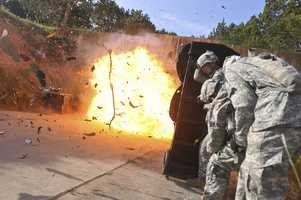 """6. Spc. Wesley A. Coble and Sgt. Victor Alcantar, combat engineers assigned to 1st Platoon, 43rd Engineer Company, 2nd Squadron """"Sabre"""", 3d Cavalry Regiment, find cover behind a """"blast blanket"""" after detonating an entryway with explosives July 31 at a subterranean tunnel complex on Fort Hood. The Soldiers were taking part in a training event designed to develop tactics, training, and procedures for emerging battlefields."""