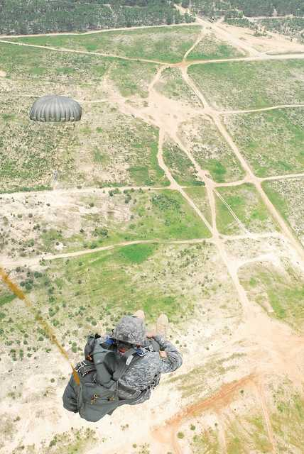 11. A Paratrooper from the 528th Sustainment Brigade, U.S. Army Special Operations Command braces for the release of the main parachute after exiting a UH-60 Black Hawk, Luzon Drop Zone, Camp Mackall, N.C., July 11.