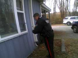 A police officer gets evidence from the window.