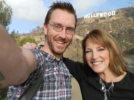 Photographer Scott Wilson and anchor/reporter Lori Burkholder pose in front of the Hollywood sign.