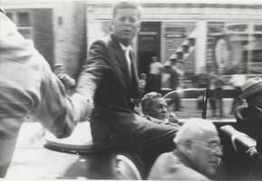 Kennedy shakes hands with someone in the crowd.
