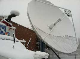 A sheet of snow clings to WGAL's main satellite dish Tuesday morning.