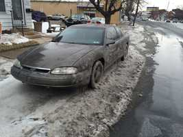 Once the main broke, water rushed into the street. As other cars passed this parked vehicle, and two others, water splashed up and froze.