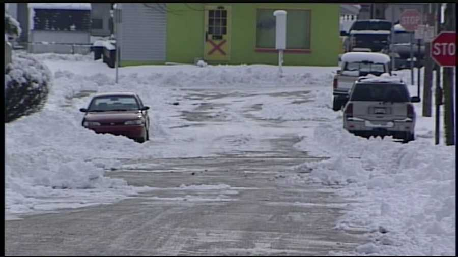 Snow piled high along the roads and some parked cars were plowed in.