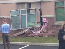 The crash caused a brick wall and windows of the building to cave in and crumble.