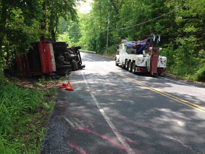 A dump truck flipped over as it headed down a curvy road in Rapho Township.