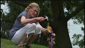 Two days after the crash, a stranger places a cross at the crash scene.