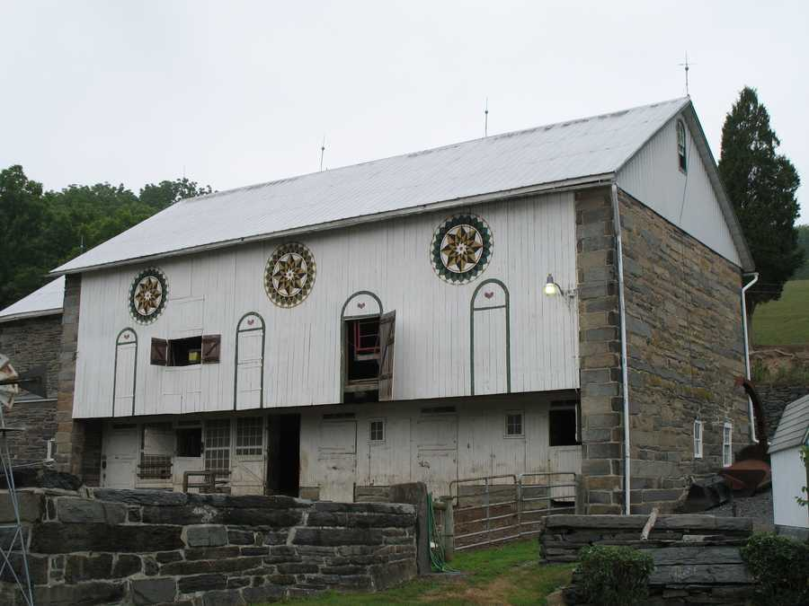The over 200-year-old practice of painting barn stars is a Pennsylvania Dutch, not Amish, tradition. Three barn stars on a Berks County barn are pictured.