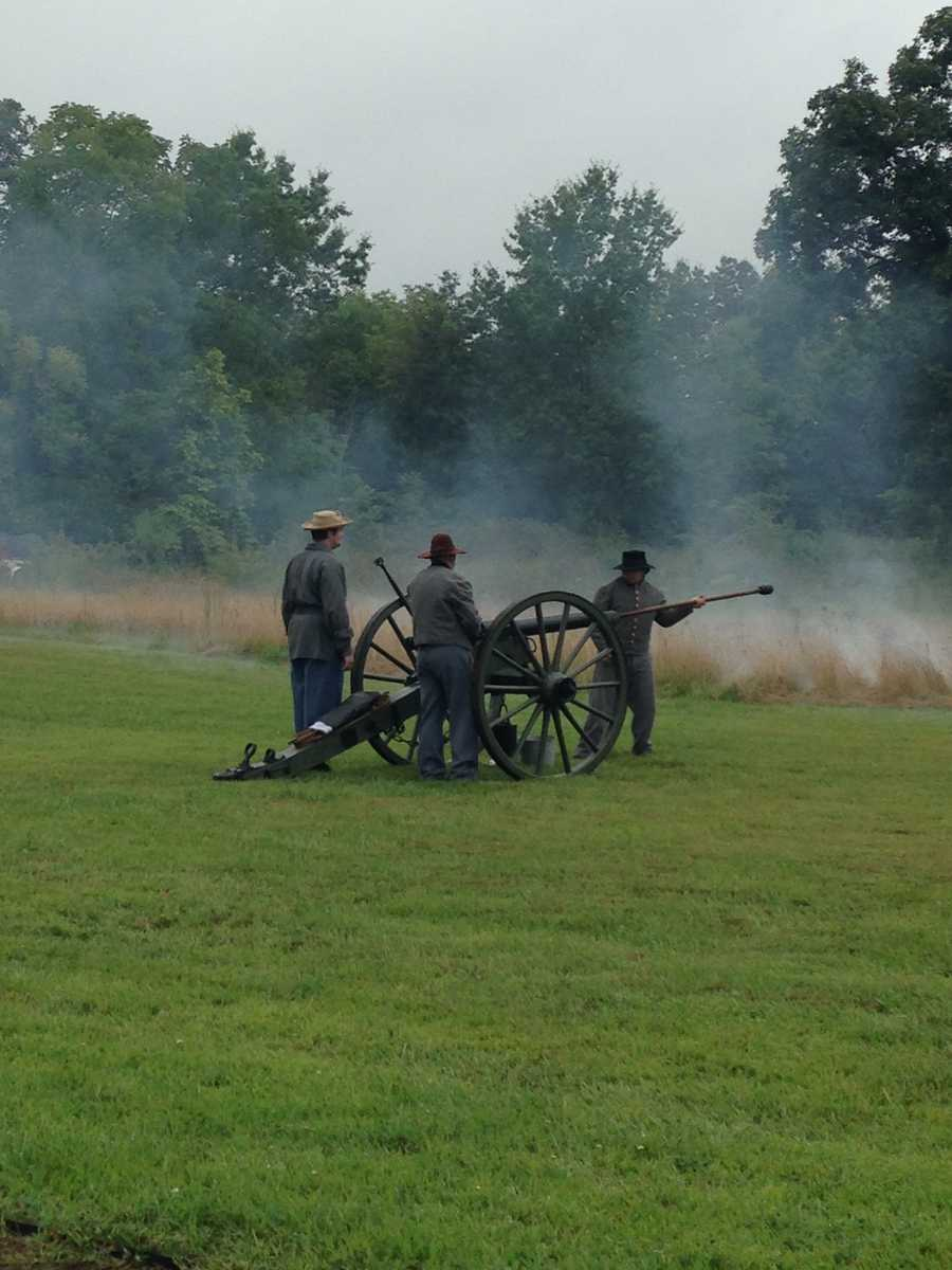 Civil War reenactors attended to the cannon.