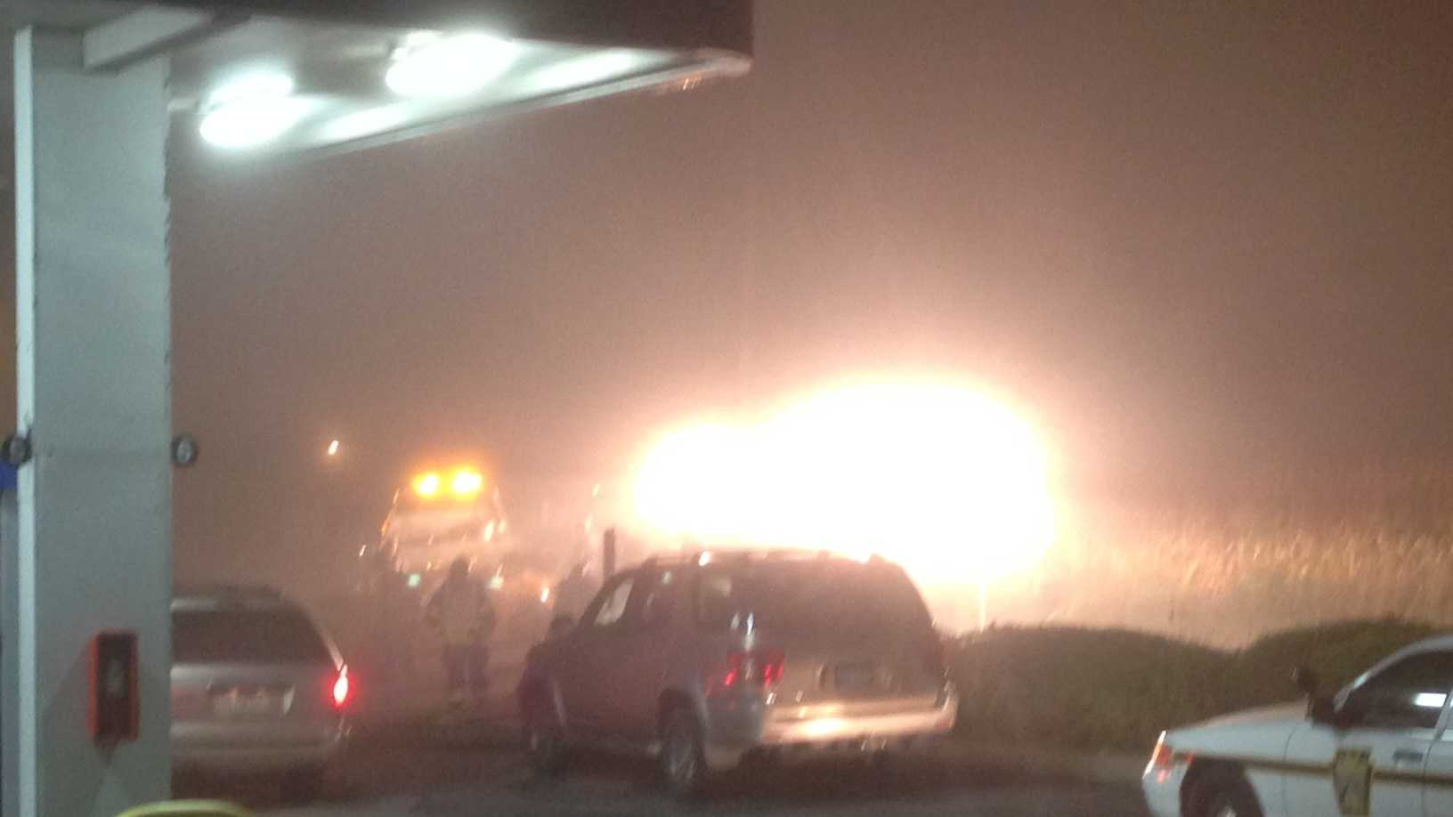 Emergency crew lights illuminate the crash scene on a foggy morning.