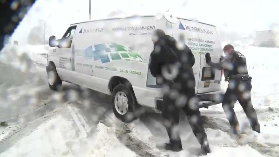 An officer and a motorist try to free a stuck van on Route 441 in Lancaster County.
