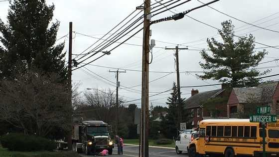 A witness sent this photo to u local. The person wrote that it looked as though the child was crossing the street to get to the bus. A person is crouching on the ground over the child, helping him.