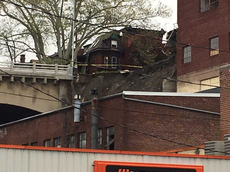 Officials say ground gave-way near the bridge, which caused the car to land on a Cameron Street business. The incident caused a portion of the building, which houses a tire store, to collapse.