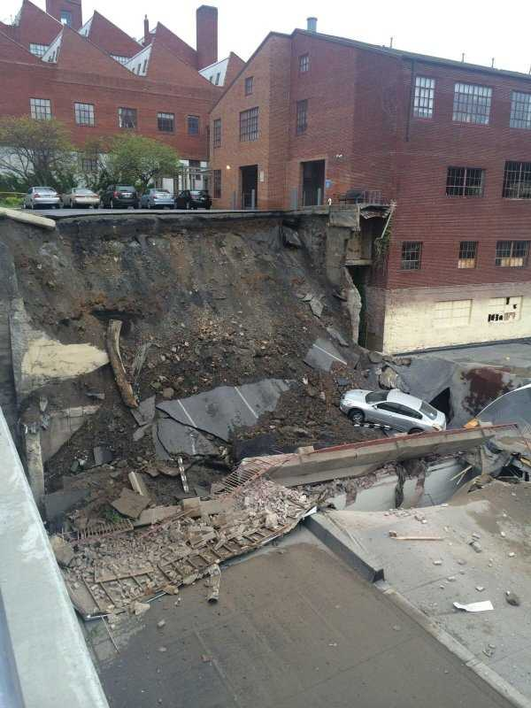 A parking lot caved-in near the Mulberry Street Bridge in Harrisburg Thursday afternoon and sent a car onto the roof of a tire shop. Photo Credit: Mayor Eric Papenfuse/Official Twitter Page (@EricPapenfuse)