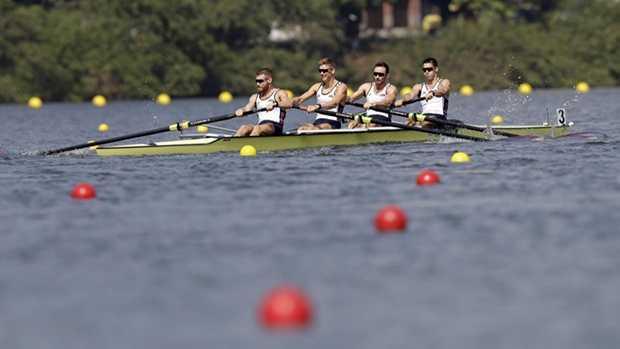 AP Photo: Tyler Nase, far left, rows with the four-man team.