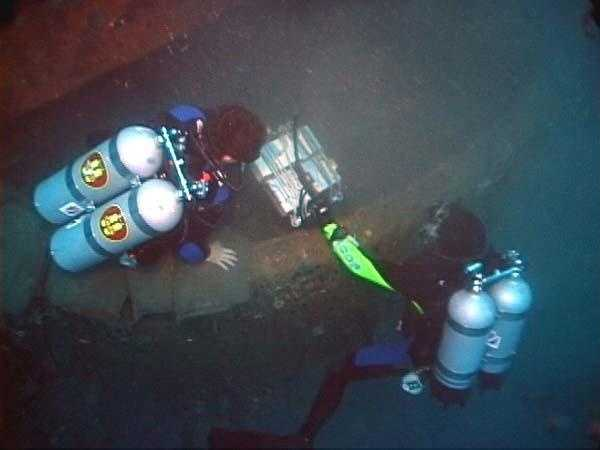 NOAA divers guided a sub-bottom profiler around the turret, searching for historic objects buried in sediment. This marked the first-ever successful diver-assisted sub-bottom profiler survey at any depth. And this one was conducted at 240 ft! The profiler was tethered by cable to a research vessel. On board, images were viewed via computer.