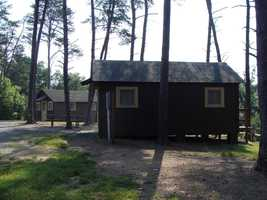 The cottages have a dining table and chairs, wooden floors, windows, electric heat, a picnic table and fire ring outside, electric lights and outlets.