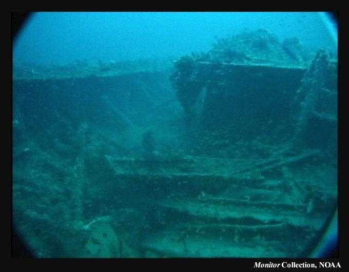 "A view across the forward area of the wreck looking aft. This shows the significant collapse of the midships bulkhead. The structure to the right is the now displaced ""turret support truss"" and marks the original location of the monitor's turret."