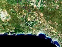 """The Nardo Ring is a striking visual feature from space, and astronauts have photographed it several times. The Ring is a race car test track that is steeply banked to reduce the amount of active steering needed by drivers. The Ring lies in a remote area on the heel of Italy's """"boot,"""" east of the naval port of Taranto and encompasses a number of active (green) and fallow (brown to dark brown) agricultural fields."""