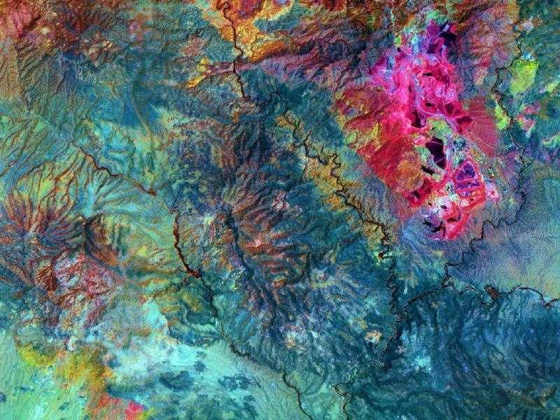 Looking more like an alien landscape than an Earthly landscape, the Morenci open-pit copper mine in southeast Arizona is North America's leading producer of copper. This ASTER image uses short wavelength infrared bands to highlight in bright pink the altered rocks in the Morenci pit associated with copper mineralization.