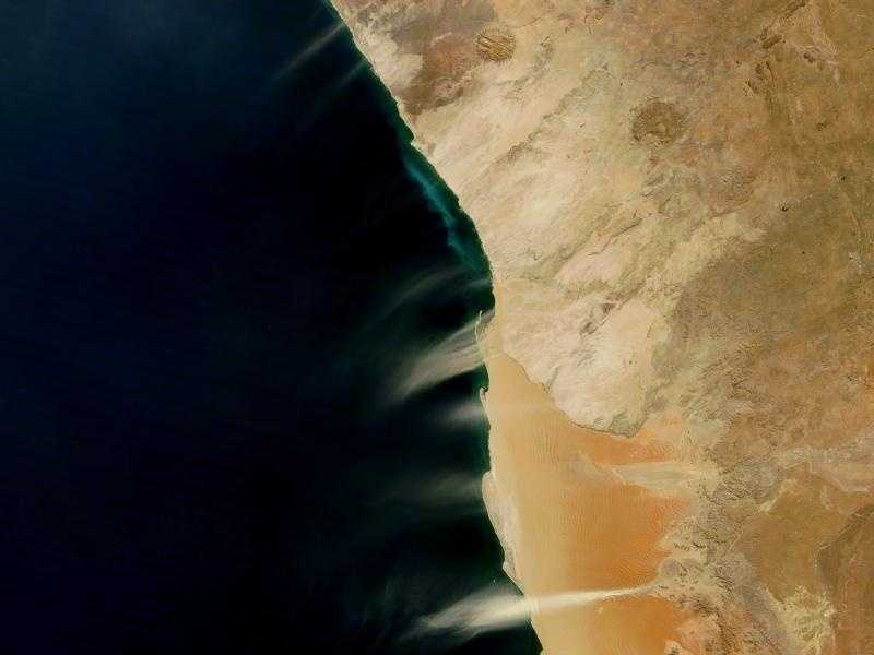 Cloudless skies allowed a clear view of dust and hydrogen sulfide plumes along the coast of Namibia in early August 2010. Multiple dust plumes blow off the coast toward the ocean, most or all of them probably arising from streambeds. Unlike the reddish-tan sands comprising the dunes directly south of the Kuiseb River, the stream-channel sediments are lighter in color. Wind frequently pushes dust plumes seaward along the Namibian Coast. Easterly trade winds blow from the Indian Ocean over the African continent, losing much of their moisture as they go. The winds are hot and dry as they pass over Namibia's coastal plain, where they are prone to stir fine sediments.