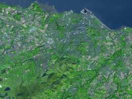 """Once a medieval fortress, Scotland's Edinburgh is nicknamed """"Athens of the North."""" Today, the city preserves landmarks from centuries past, as well as the remains of geologic processes that occurred millions of years ago. Both human and natural impacts on the area are visible from space. Edinburgh's proximity to the sea gives the city a mild climate, with average daily lows that remain above freezing, and similarly mild summertime temperatures."""