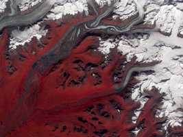Alaska's Susitna Glacier revealed some of its long, grinding journey when the ASTER on NASA's Terra satellite passed overhead on Aug. 27, 2009. The glacier surface appears especially complex near the center of the image, where a tributary has pushed the ice in the main glacier slightly southward. Susitna flows over a seismically active area
