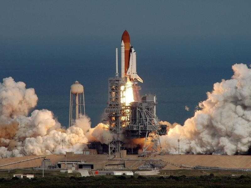 Against a backdrop of blue Atlantic Ocean, space shuttle Atlantis carrying its crew of seven rises majestically from Launch Pad 39A at NASA's Kennedy Space Center.