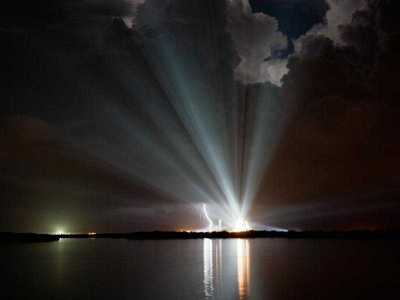 Xenon lights over Launch Pad 39A at NASA's Kennedy Space Center in Florida compete with the lightning strike seen to the left. Space shuttle Discovery was on the pad waiting for a scheduled liftoff.