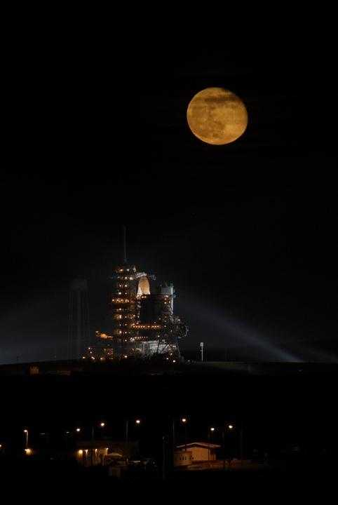 Above Launch Pad 39A at NASA's Kennedy Space Center in Florida, the full moon hovers over space shuttle Endeavour waiting for liftoff on the STS-126 mission.