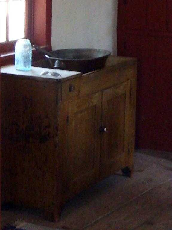 A wash basin sits beneath the window. The basin would have to be filled with water since there was no plumbing in the little home.