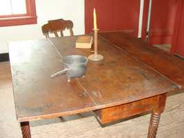 This table is located in the main room, near the fireplace.
