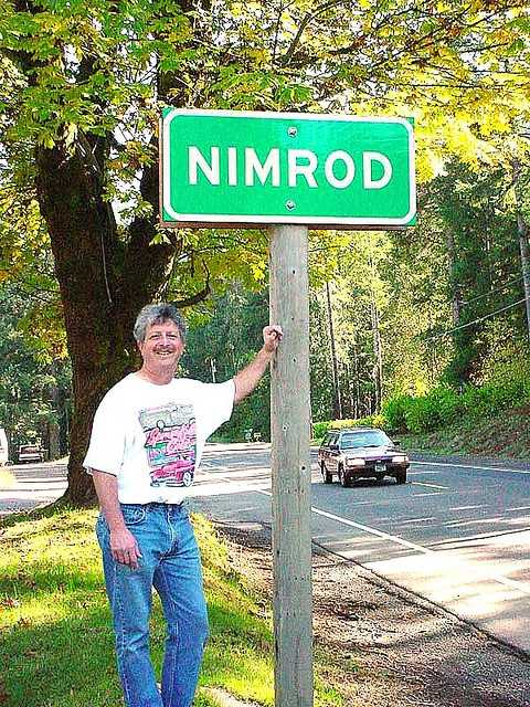 The sign is for the city, and not the guy underneath. Welcome to Nimrod, Minnesota.