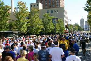 The Marquette Men's basketball team (blue & gold jackets on the right side) cheered on participants as they ran/walked past.