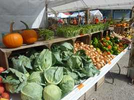 A farmers market area is set up with a wide variety of seasonal crops.