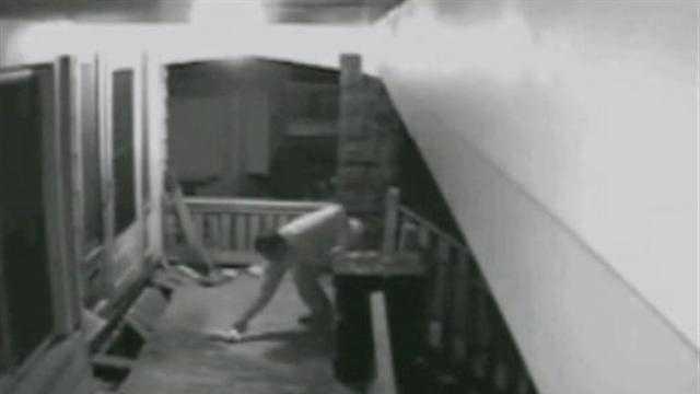 Surveillance camera captures man igniting fire on porch.
