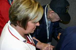 Paula Nelson, Stars and Stripes Honor Flight Secretary, helps one of the vets off the plane.