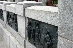There are 24 bronze bas-relief panels that depict wartime scenes of combat and the home front.