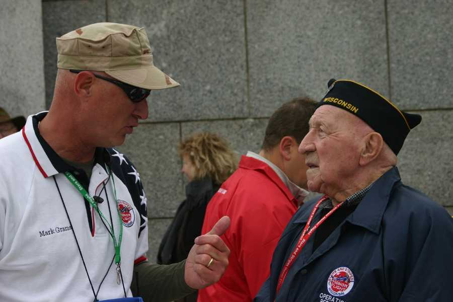 Mark Grams, a Stars and Stripes Honor Flight board member, talks to a veteran at the memorial.