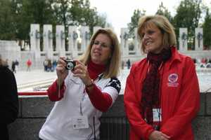 Amy Klapper (left), a Stars and Stripes Honor Flight board member, stands near the Wisconsin pillar to help take photos of the veterans and their guardians.