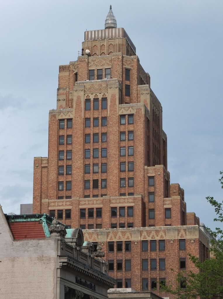 The Wisconsin Gas Building (formerly the Milwaukee Gas Light Building) is a classic stepped Art Deco tower located downtown. It was designed by architects Eschweiler & Eschweiler and completed in 1930 using differing materials on the exterior to graduate from dark to light. A weather beacon shaped as a natural gas flame was added to the top of the Wisconsin Gas Building in 1956 which indicates the forecast of the weather by its color and flicker. The flame was turned off in 1973 due to the energy crisis and turned back on again in 1985. Its neon flame stands 21 feet tall and weighs in at four tons.