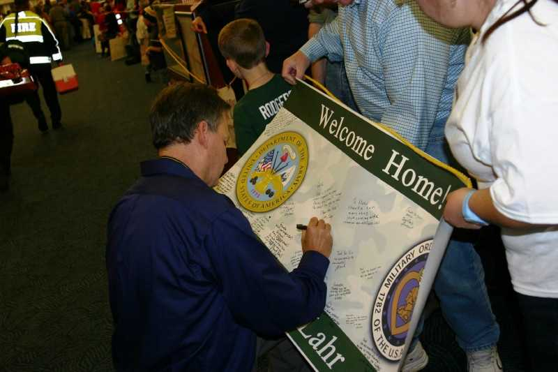 Joe Dean, founder of Stars and Stripes Honor Flight, autographs someone's sign at the homecoming.