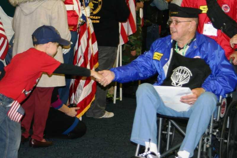 Veterans with light blue jackets are Korean War vets.