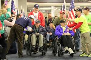Flags, music, cheering and lots of hugs and handshakes await the vets.
