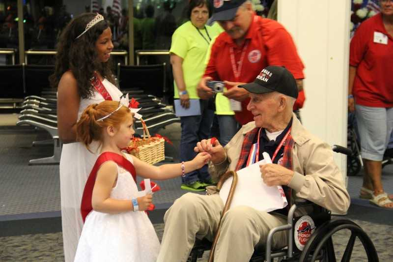 The Poppy Princesses hand out poppies to each vet as they return home.